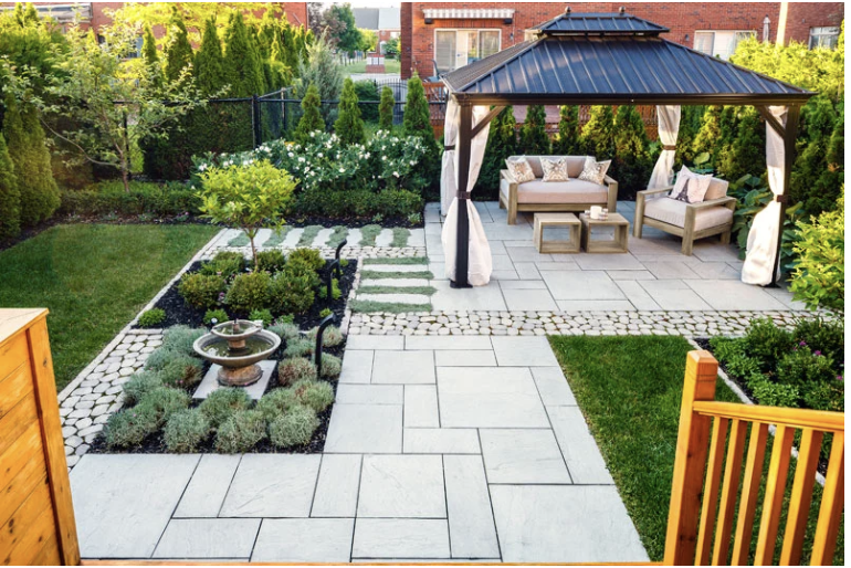 Outdoor living space with pergola and Techo-Bloc pavers, with water feature.