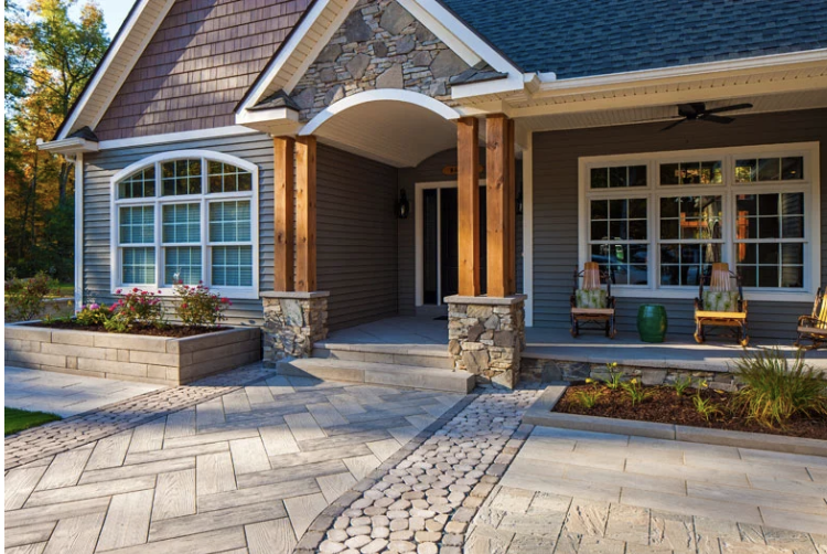 Rustic yet charming front entrance, with Techo-Bloc paving stones, wood pillars, and a touch of stone veneer.