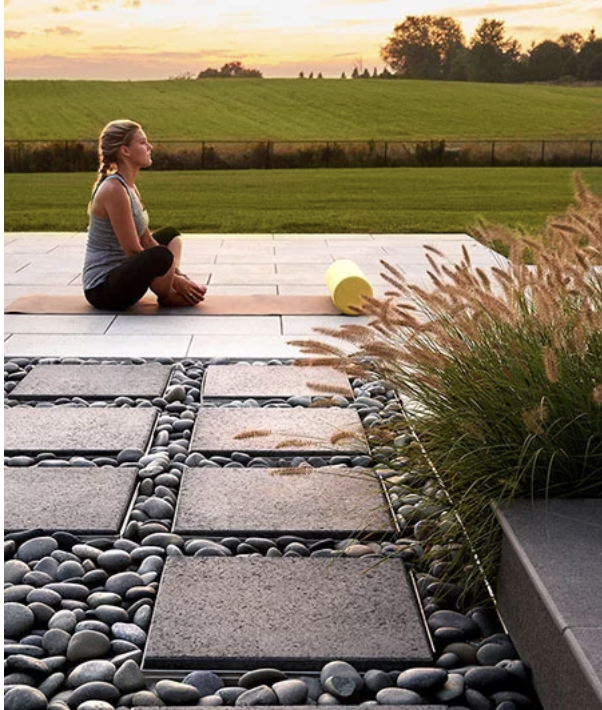 Stepping stones, framed by imported ornate pebbles, with a touch of foliage make an outdoor dream come true.